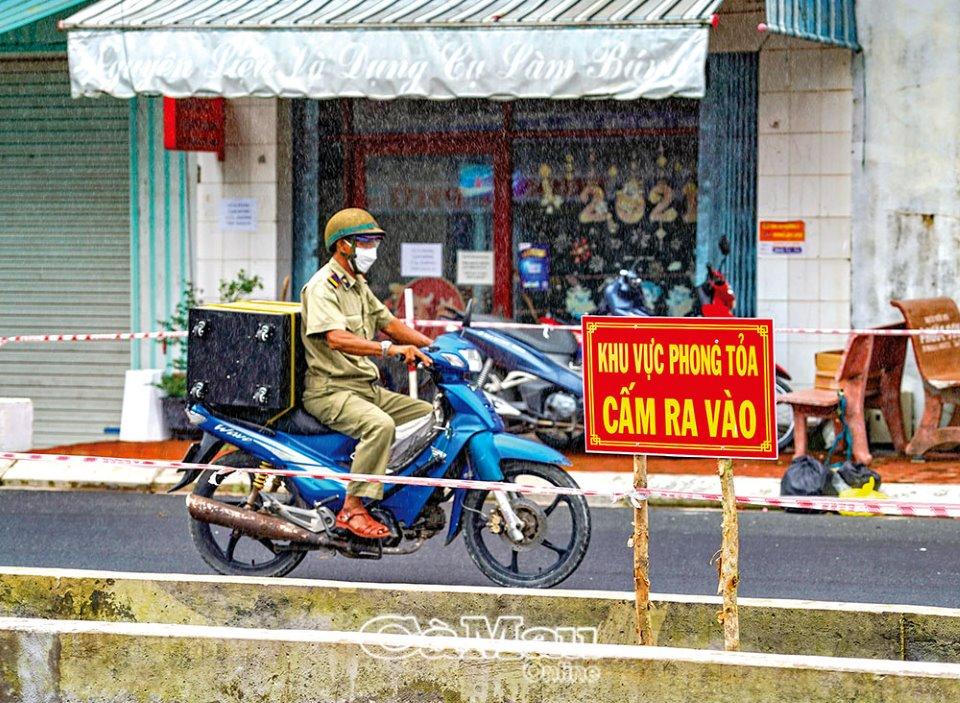 Lực lượng trực gác chốt dùng loa di động thông báo những thông tin cần thiết đến người dân trong khu vực phong toả.